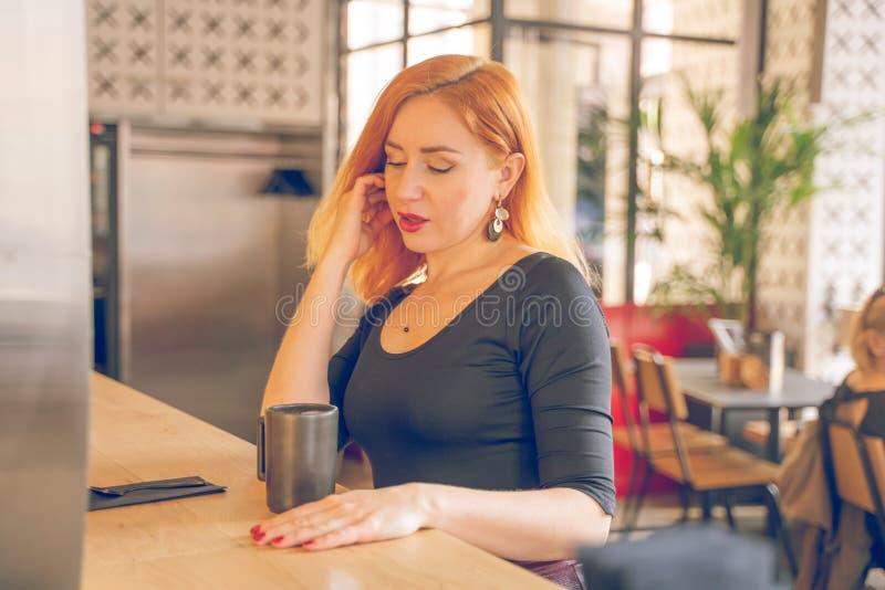 Mujer cauc?sica redheaded feliz bonita en la taza negra de las bebidas de la camisa de caf? en el caf? moderno solamente imagen de archivo