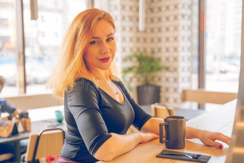 Mujer cauc?sica redheaded feliz bonita en la taza negra de las bebidas de la camisa de caf? en el caf? moderno solamente fotografía de archivo