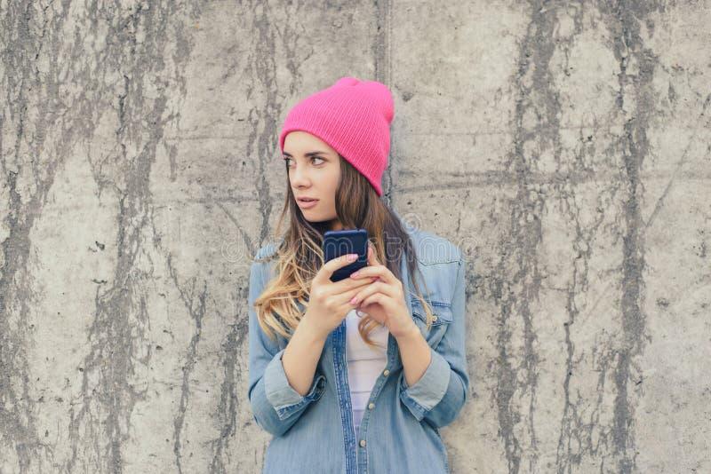 Mujer celosa que comprueba su teléfono móvil del ` s del novio SMS secreto de la lectura de la mujer en su teléfono móvil La vist foto de archivo