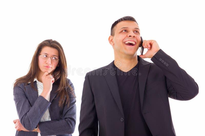 Mujer celosa que mira a su hombre que habla en el teléfono imagen de archivo libre de regalías