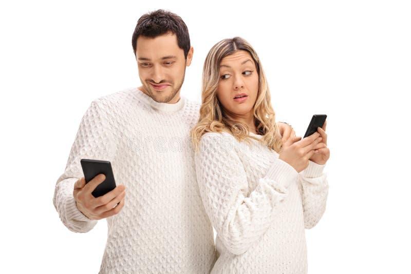 Mujer celosa que mira su teléfono de los boyfriend's fotografía de archivo libre de regalías