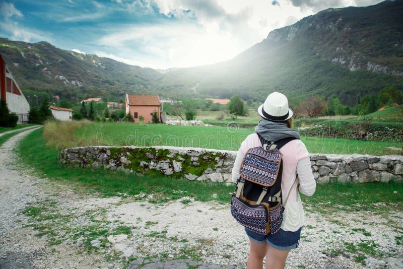 Mujer cerca de las montañas y del pueblo del campo fotos de archivo