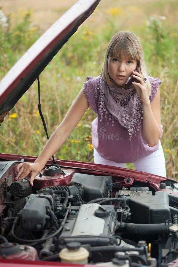 Mujer cerca de su coche quebrado fotografía de archivo