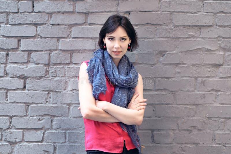 Mujer cerca de una pared de ladrillo foto de archivo libre de regalías