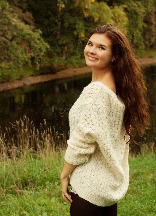 Mujer cerca del río en la estación del otoño imagenes de archivo