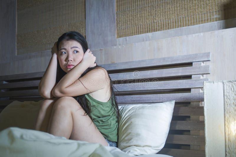 Mujer china asiática asustada y subrayada hermosa joven que tiene sentada del insomnio despierta en pesadilla sufridora insomne d foto de archivo