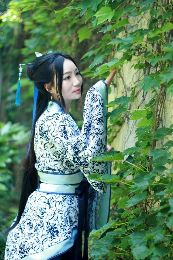Mujer china asiática en el vestido azul y blanco tradicional de Hanfu, juego en un jardín famoso cerca de la pared fotos de archivo
