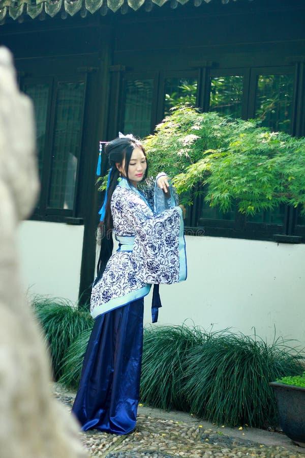 Mujer china asiática en el vestido azul y blanco tradicional de Hanfu, juego en un jardín famoso cerca de ventanas foto de archivo