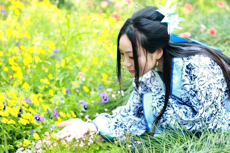 Mujer china asiática en el vestido azul y blanco tradicional de Hanfu, juego en un jardín famoso, colocándose entre las flores foto de archivo
