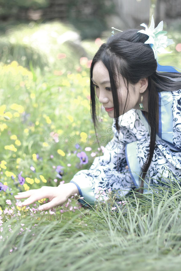 Mujer china asiática en el vestido azul y blanco tradicional de Hanfu, juego en un jardín famoso, colocándose entre las flores fotos de archivo