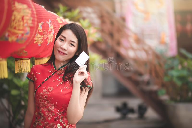 Mujer china asiática en el vestido rojo tradicional de Cheongsam que lleva a cabo el crédito en blanco para hacer compras en Año  foto de archivo