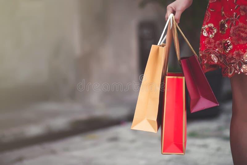 Mujer china asiática en el vestido rojo tradicional de Cheongsam que sostiene el bolso de compras en festival chino del Año Nuevo imagen de archivo libre de regalías
