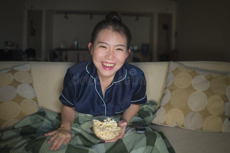 Mujer china asiática feliz y alegre hermosa joven que mira la película de la comedia de la TV o la demostración hilarante que ríe imagen de archivo libre de regalías