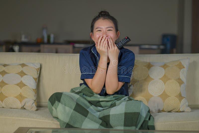Mujer china asiática feliz y alegre hermosa joven que mira la película de la comedia de la TV o la demostración hilarante que ríe imágenes de archivo libres de regalías