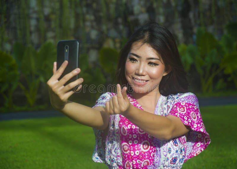 Mujer china asiática feliz y hermosa joven que toma imagen del selfie con la cámara del teléfono móvil que hace la muestra del am imágenes de archivo libres de regalías