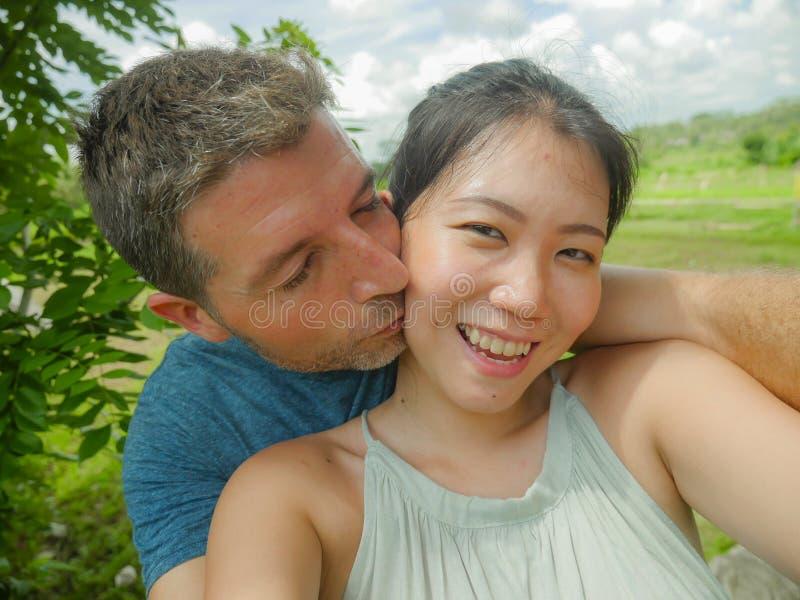 Mujer china asiática hermosa joven de los pares mezclados hermosos y felices de la pertenencia étnica y hombre blanco en el amor  fotografía de archivo