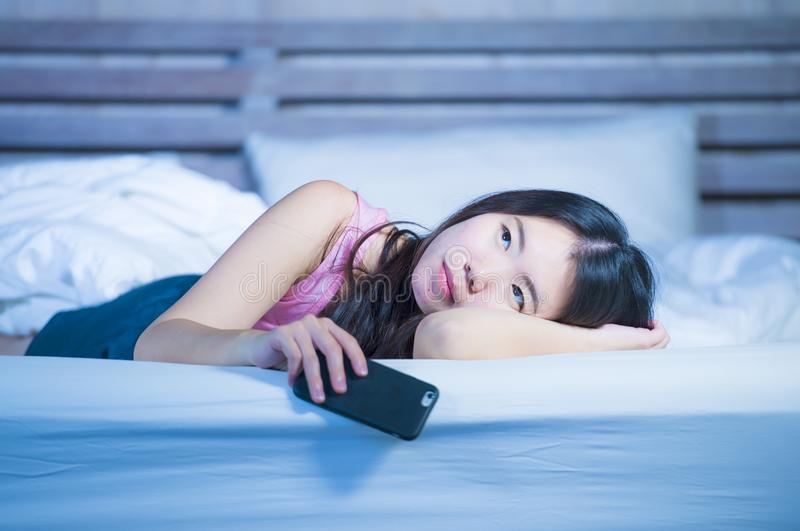 Mujer china asiática hermosa y pensativa joven en su 20s que sostiene el teléfono móvil que miente en cama en parecer de pensamie fotografía de archivo libre de regalías