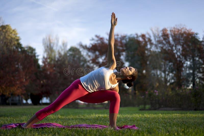 Mujer china asiática que hace yoga en naturaleza durante puesta del sol imágenes de archivo libres de regalías