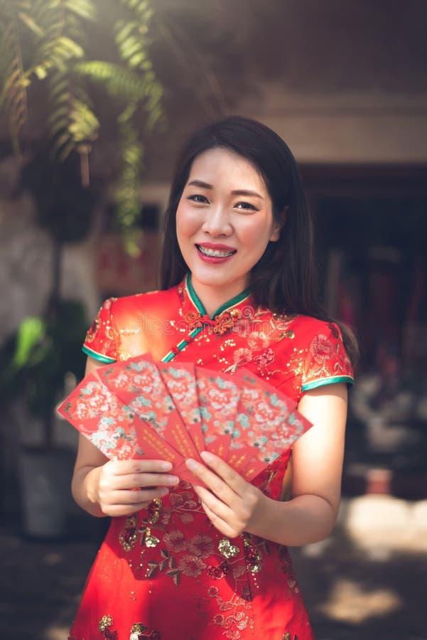 Mujer china asiática que lleva el vestido rojo tradicional de Cheongsam que sostiene el sobre rojo para dar a Ang Pao en Año Nuev fotos de archivo