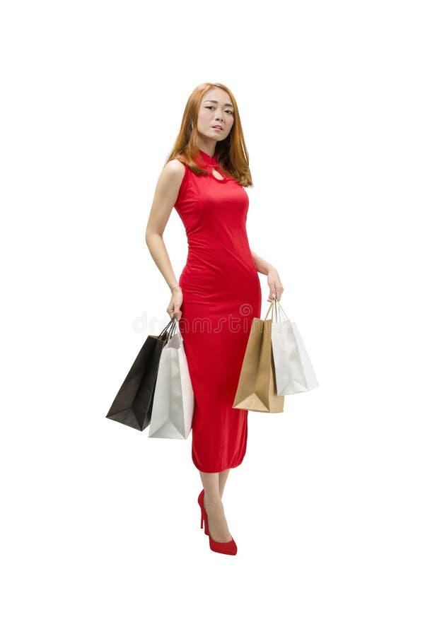Mujer china bonita con el vestido del cheongsam que sostiene bolsos de compras foto de archivo libre de regalías