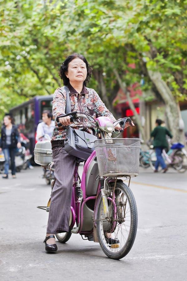 Mujer china de la Edad Media en la bici eléctrica con la cesta, Yangzhou, China imágenes de archivo libres de regalías