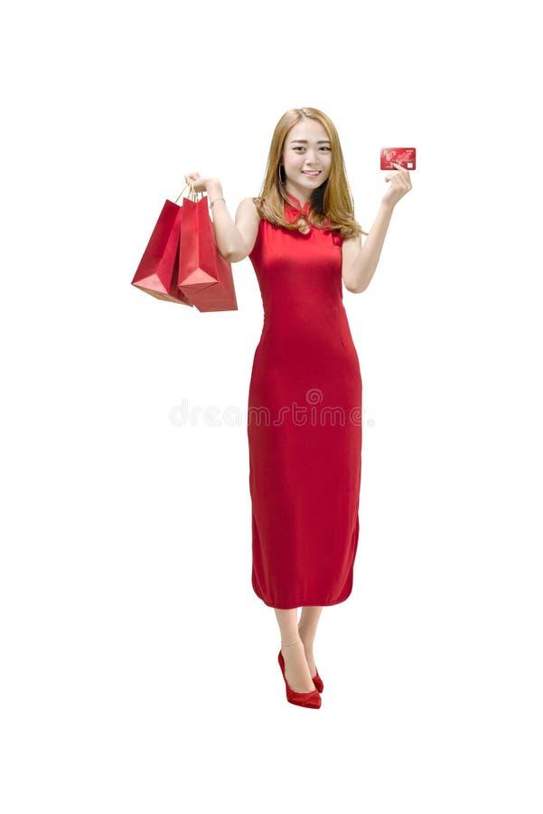 Mujer china del retrato con el vestido del cheongsam que sostiene vagos de papel rojos imagenes de archivo