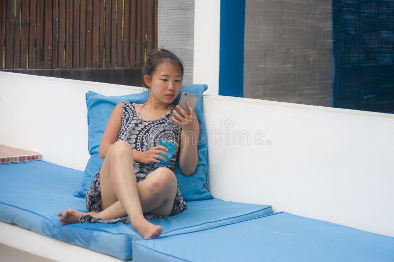 Mujer china dulce y bastante asiática joven que se sienta en el centro vacacional de la playa usando medios sociales de Internet  imagen de archivo