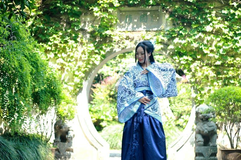 Mujer china en el vestido azul y blanco tradicional de Hanfu que se coloca en el medio de la puerta hermosa imagenes de archivo