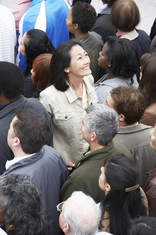 Mujer china que hace frente a la otra dirección de la muchedumbre multiétnica fotos de archivo