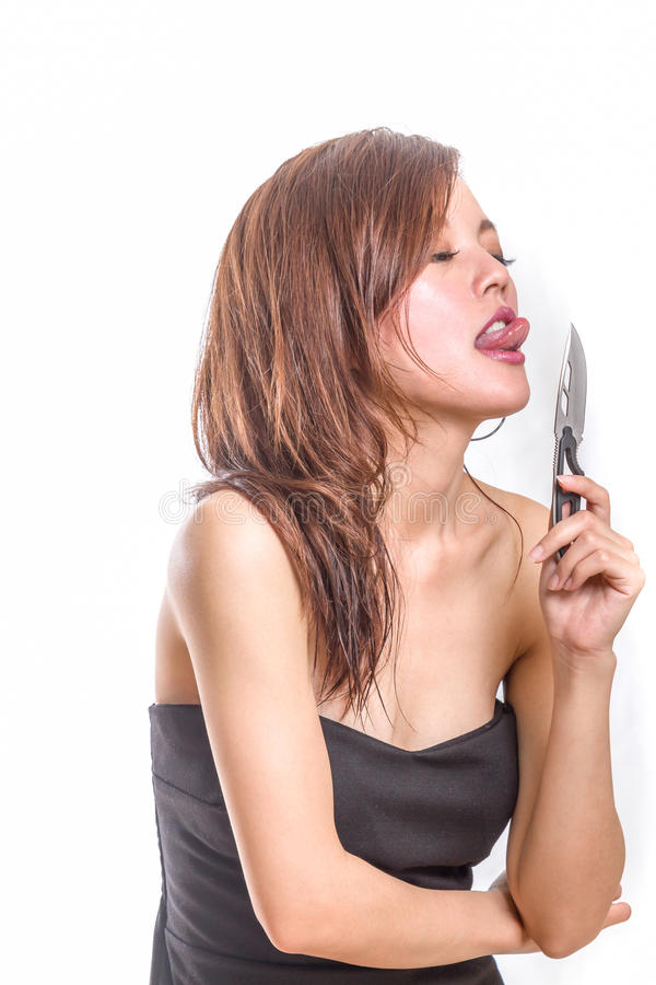 Mujer china que lame un cuchillo fotografía de archivo libre de regalías