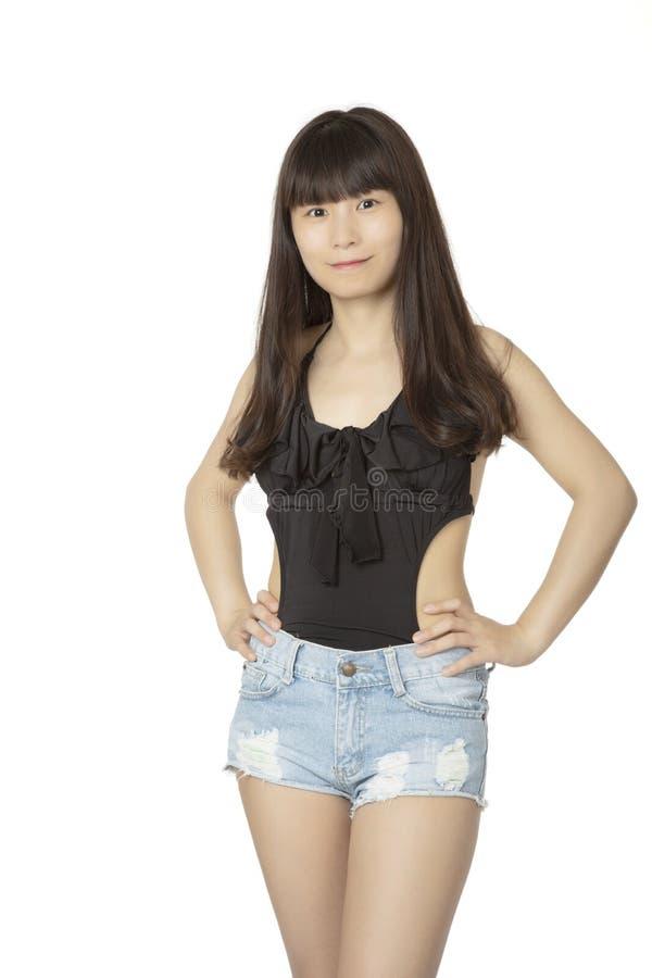 Mujer china que lleva el traje de baño de una pieza negro aislado en un wh imagen de archivo