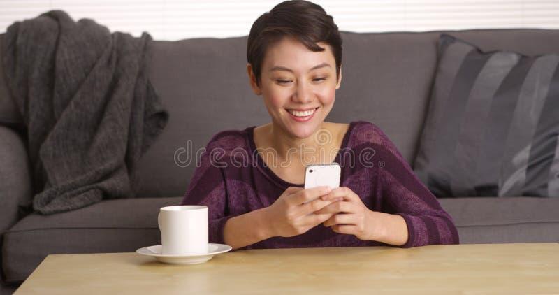 Mujer china que manda un SMS en smartphone por la mesa de centro foto de archivo