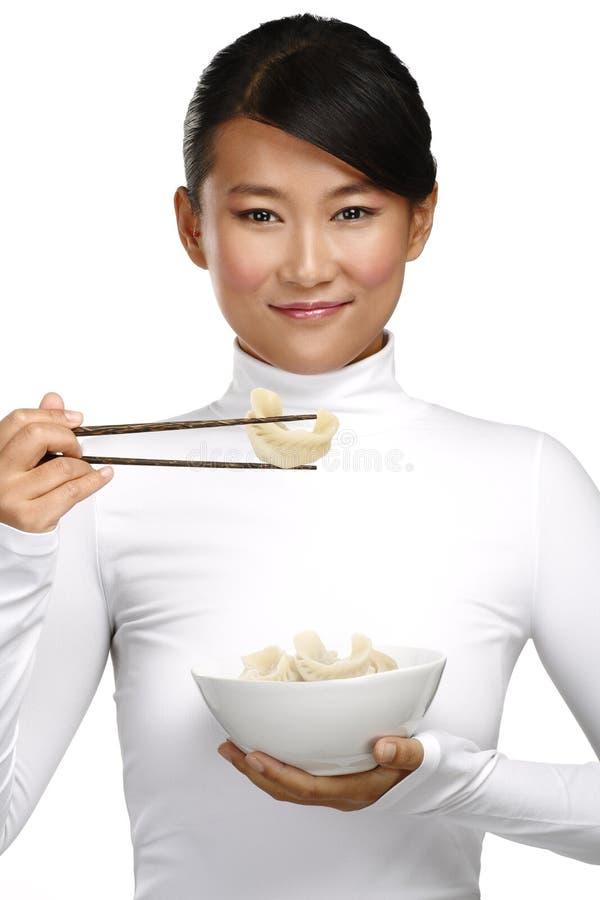 Mujer china que muestra la comida asiática usando el palillo imagenes de archivo