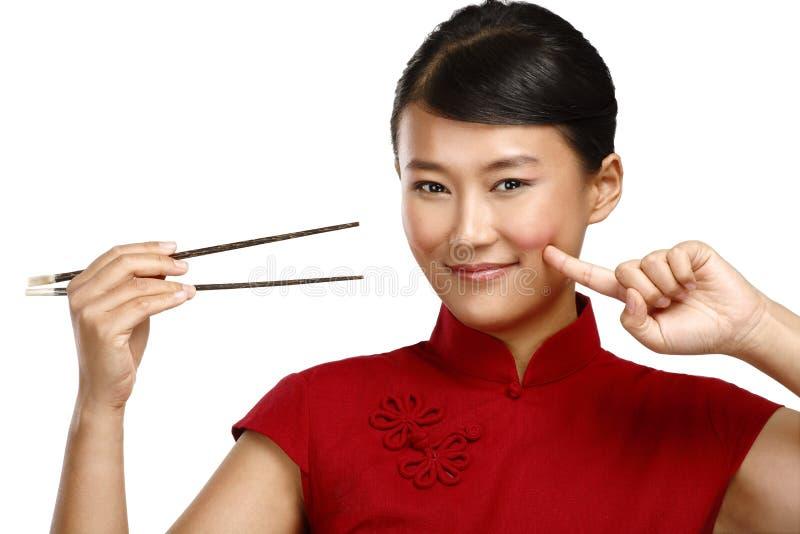 Mujer china que muestra la comida asiática usando el palillo fotos de archivo libres de regalías