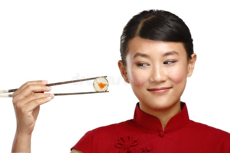 Mujer china que muestra la comida asiática usando el palillo imágenes de archivo libres de regalías