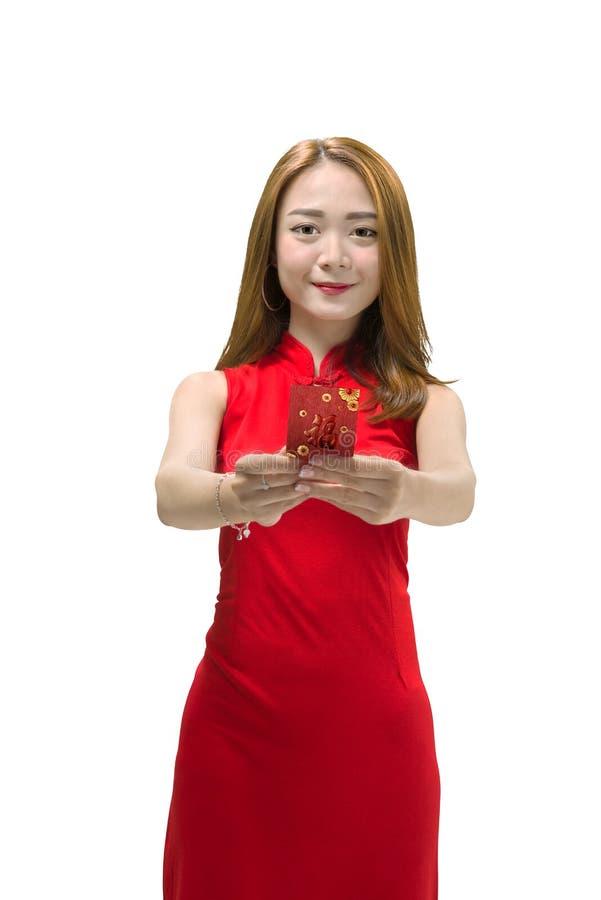 Mujer china sonriente en el vestido del cheongsam que sostiene sobres rojos imagenes de archivo