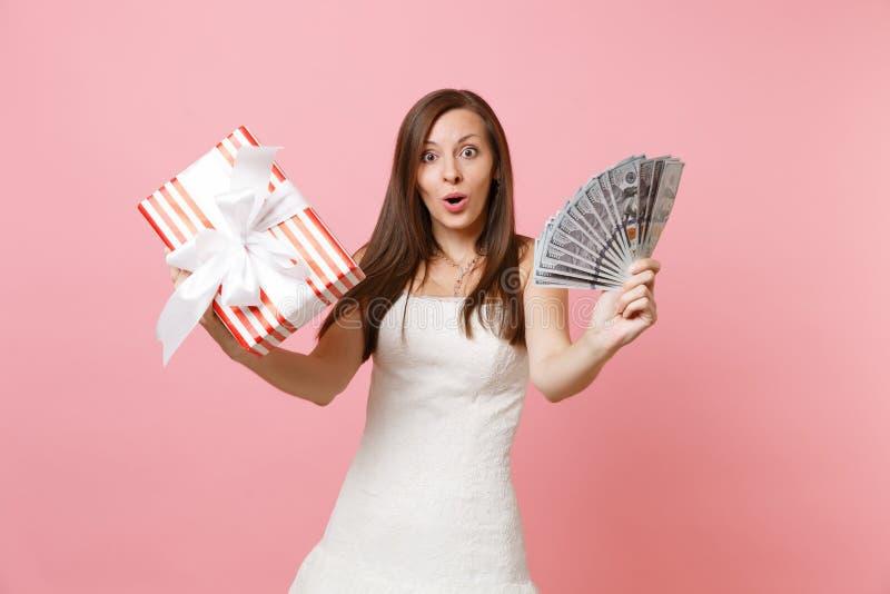 Mujer chocada Amazed de la novia en el vestido que se casa blanco que lleva a cabo porciones del paquete de dólares, dinero del e foto de archivo libre de regalías