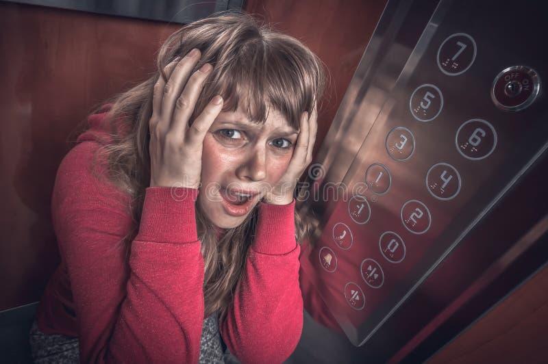 Mujer chocada con claustrofobia en el elevador m?vil foto de archivo libre de regalías