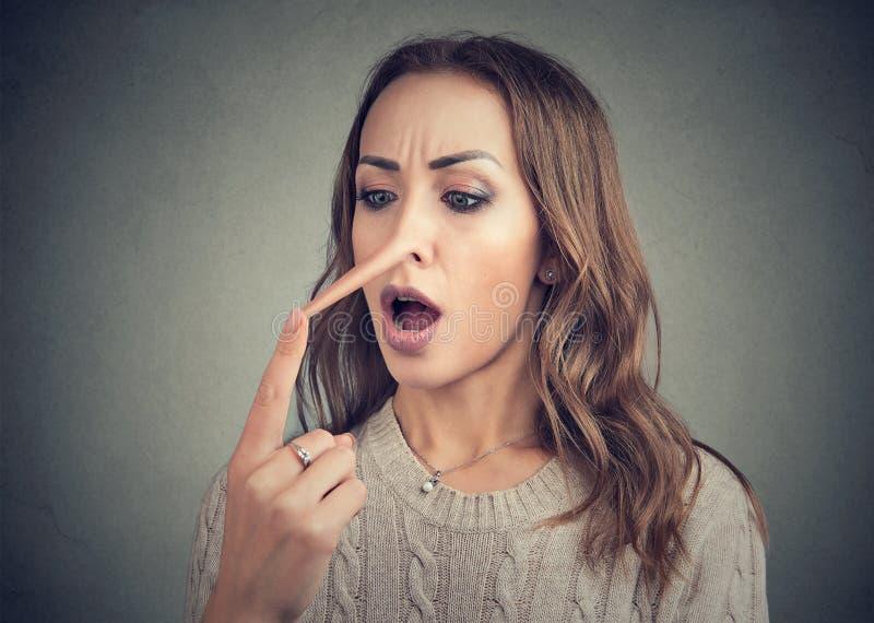 Mujer chocada con la nariz larga del mentiroso fotografía de archivo