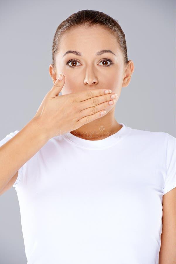 Mujer chocada con su mano a su boca foto de archivo