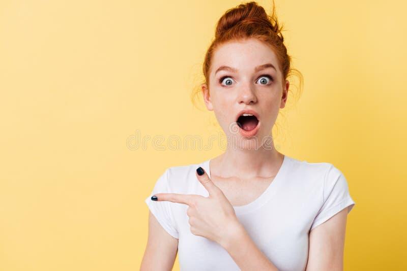 Mujer chocada del jengibre en camiseta que señala lejos imagen de archivo