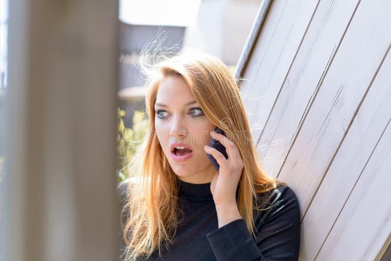 Mujer chocada durante la conversación sobre el teléfono móvil fotos de archivo
