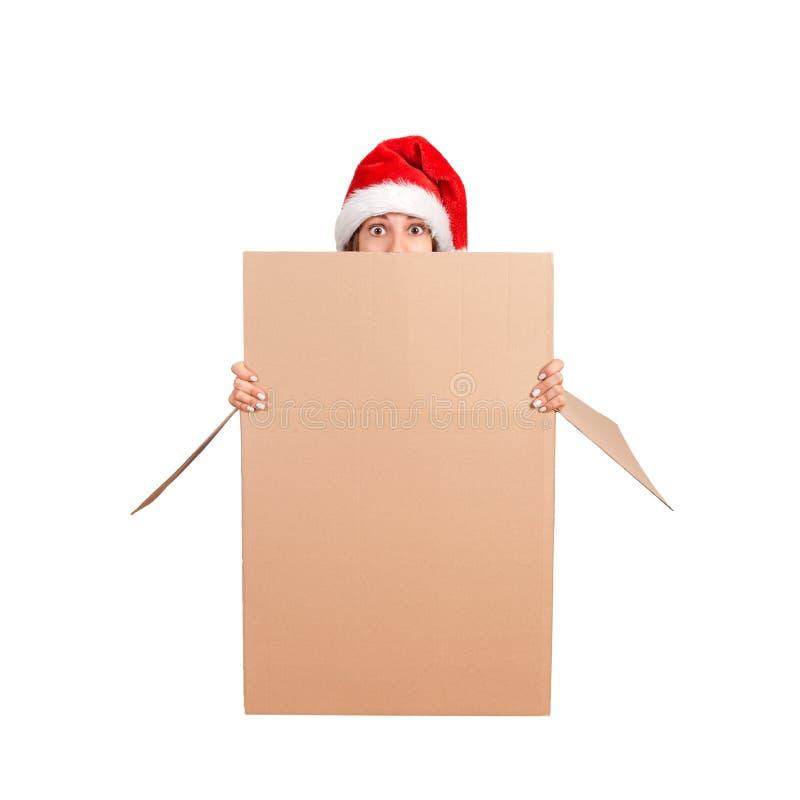 Mujer chocada en el sombrero de la Navidad que se sienta fuera de la caja de regalo grande y que mira a escondidas sobre el borde imágenes de archivo libres de regalías