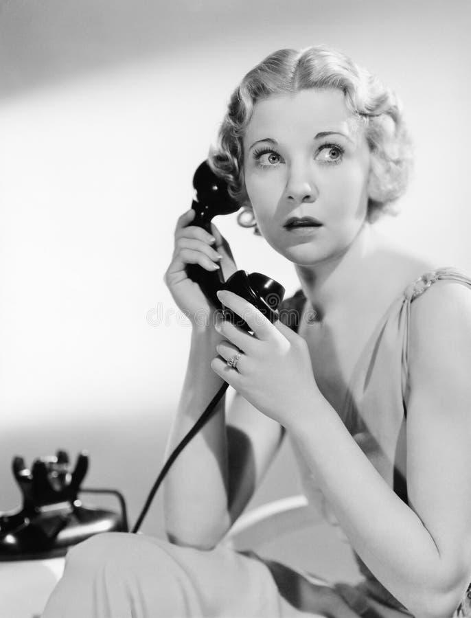 Mujer chocada en el teléfono (todas las personas representadas no son vivas más largo y ningún estado existe Garantías del provee foto de archivo libre de regalías