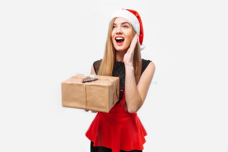 Mujer chocada en un vestido y un sombrero de Santa Claus, celebrando el Ne foto de archivo