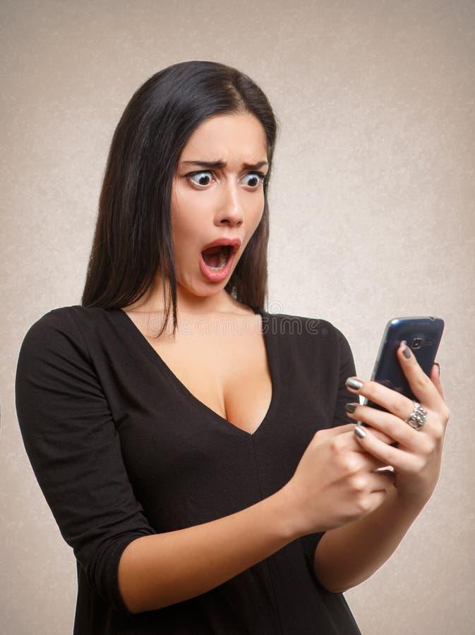 Mujer chocada por noticias o el mensaje del teléfono móvil imagenes de archivo