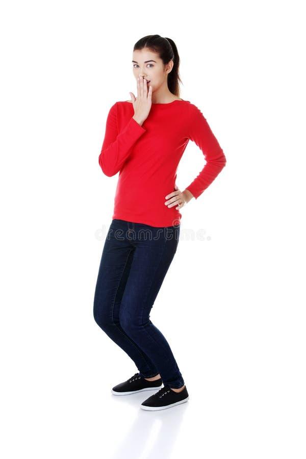Mujer chocada que cubre su boca con la mano imagen de archivo