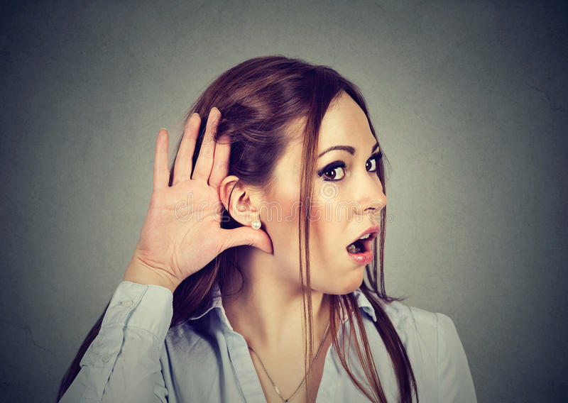 Mujer chocada que escucha detras de las puertas Concepto de las rumores y de los chismes foto de archivo libre de regalías
