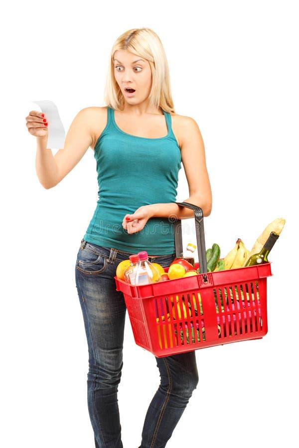 Mujer chocada que mira la cuenta de las compras fotos de archivo