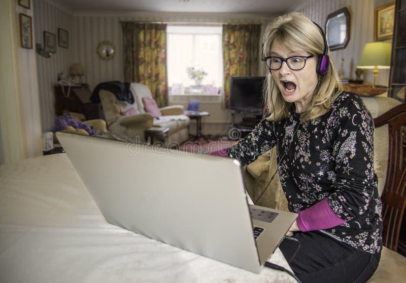 Mujer chocada que mira la pantalla del ordenador portátil imagenes de archivo